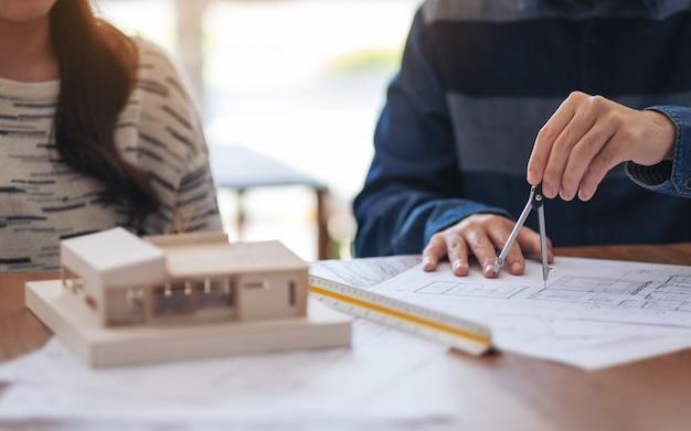 コンパスを使用してオフィスでお店の図面を描き、測定する建築家