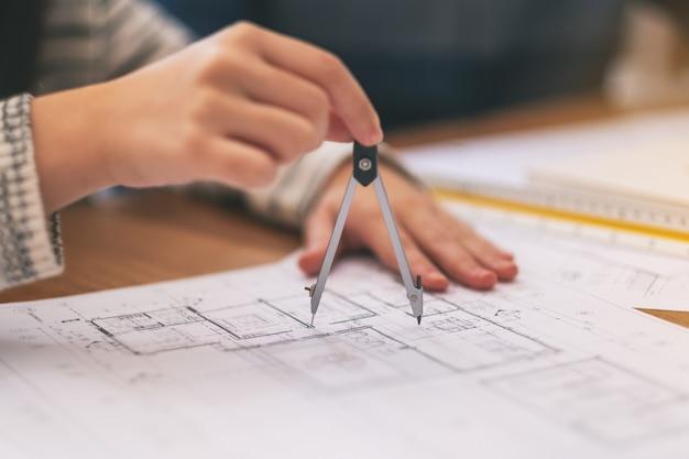 Архитектор с помощью компаса рисовал и измерял чертеж магазина в офисе