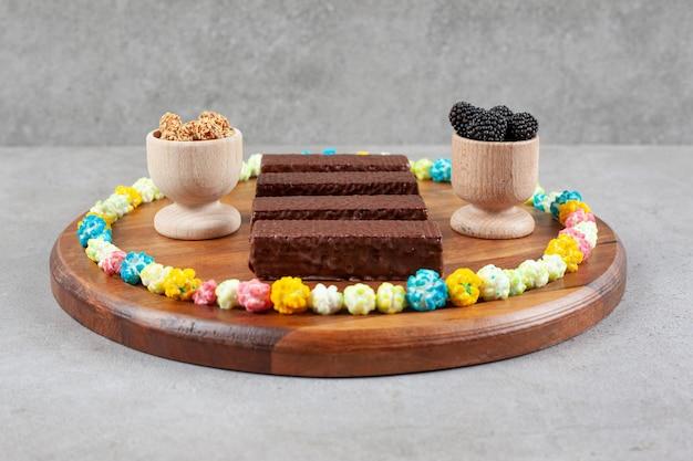 Композиция из шоколадных вафель и мисок с малиной и глазированным арахисом, окруженных конфетами, на подносе на мраморной поверхности