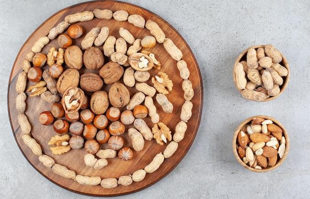 Расположение различных видов орехов на деревянной доске с чашами арахиса, миндаля и фисташек на мраморной поверхности.