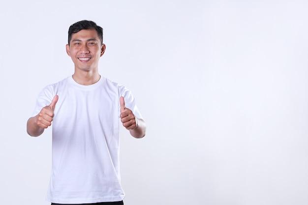 白いtシャツを着て、コピースペースで親指を見せてアジアの成人男性