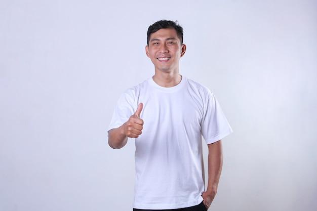 白いtシャツを着て、笑顔で親指の1つを示すアジアの成人男性