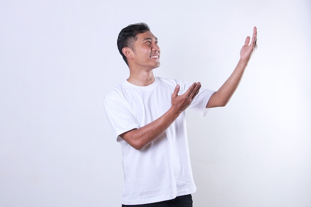 白いtシャツを着たアジアの成人男性が見つめ、笑顔で腕を横に開きます