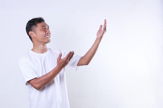 白いtシャツを着たアジアの成人男性が見つめ、コピースペースで腕を横に開きます
