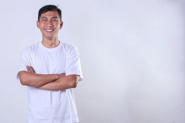 腕を組んで、コピースペースで自信を持ってジェスチャーで白いtシャツを着ているアジアの成人男性