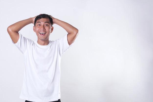 腕を組んで自信を持ってジェスチャーで白いtシャツを着ているアジアの成人男性