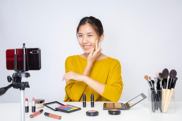 スタジオでオレンジ色の口紅を身に着けている自分のビデオを撮影しているアジアのブロガー美容ブロガー。