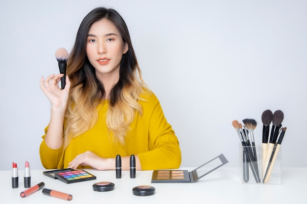 Азиатский блогер, бьюти-блогер, снимает видео, на котором она красится оранжевой помадой в студии.