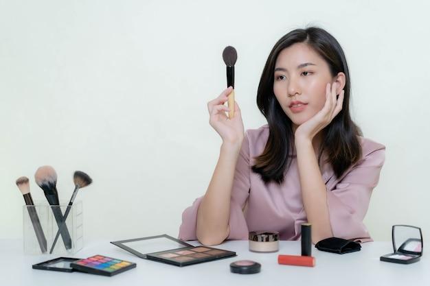 Азиатский блогер, бьюти-блогер, снимает видео, на котором она красится в студии с оранжевой помадой.
