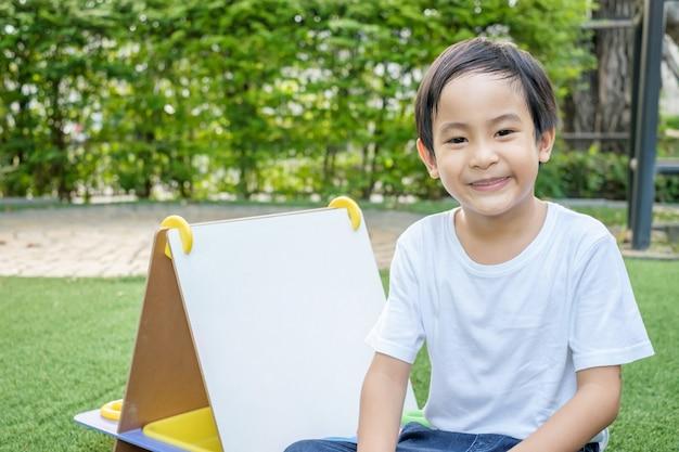 白いtシャツとジーンズのアジアの少年が芝生に座っています