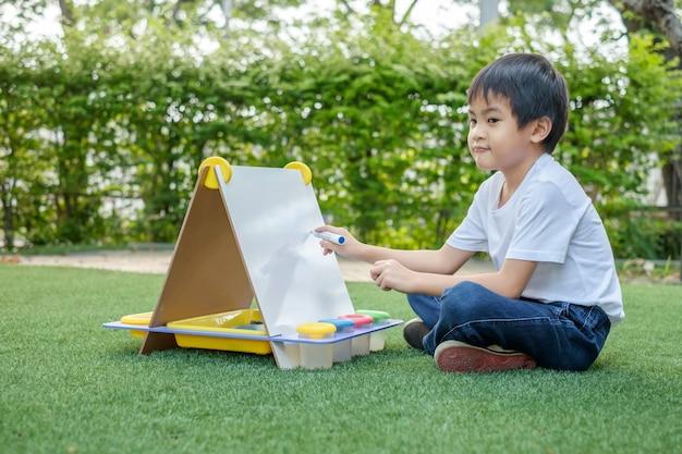 白いtシャツとジーンズを着たアジアの少年が芝生のホワイトボードに絵を描いて外に座っています。