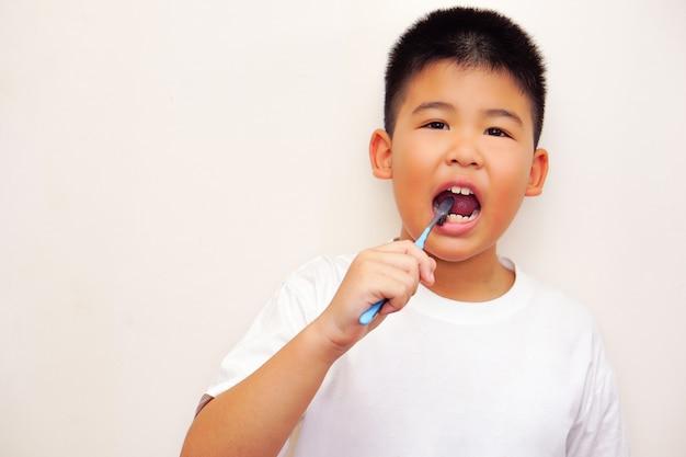 白いtシャツを着たアジアの少年が歯を掃除してカメラを見ています(白い背景)。清潔さと衛生の概念。