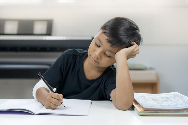 Азиатские мальчики в раненных руках устали писать записную книжку