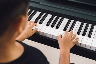An asian boys  playing the piano