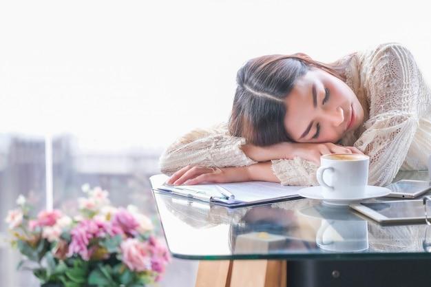 Азиатский бизнесмен сел в кофейню и спал.