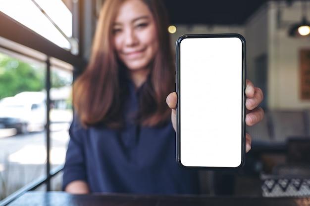 カフェで空白の画面と黒の携帯電話を保持していると示すアジアの実業家