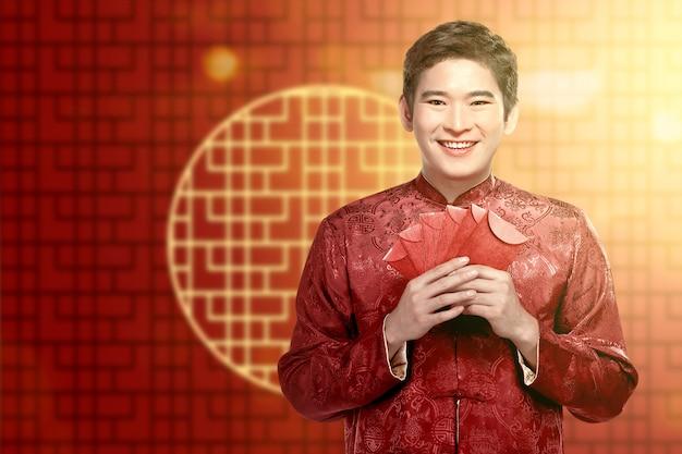 Азиатский китаец в платье чонсам держит красные конверты
