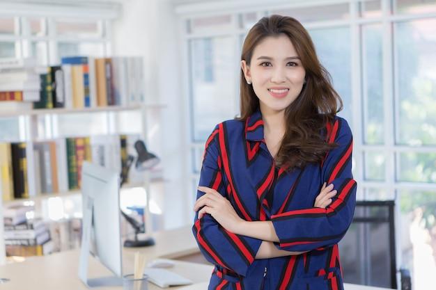 자신감 있는 아시아 여성 사업가가 집에 있는 작업실에서 팔짱을 끼고 웃고 있다