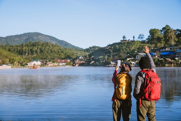朝、湖に昇る霧を眺めながら立っているアジア人カップル、トラベルネイチャー。湖の写真を撮ります。