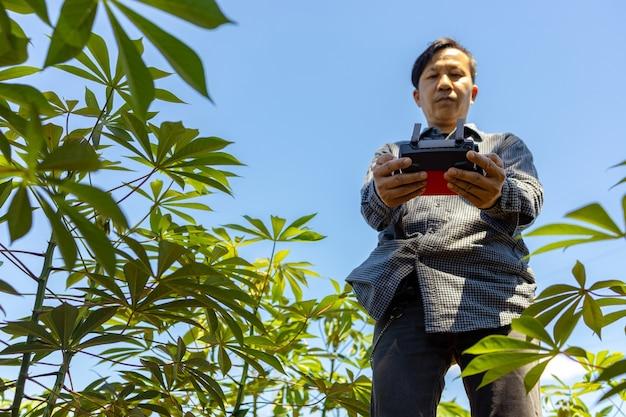 아시아 농부는 농업용 드론을 사용하여 농장에서 재배하는 작물의 손상과 성장을 감지합니다.