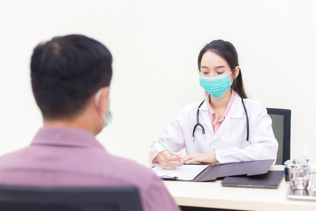 아시아 여성 의사가 병원 진찰실에서 남성 환자의 질병에 대해 질문하고 있다