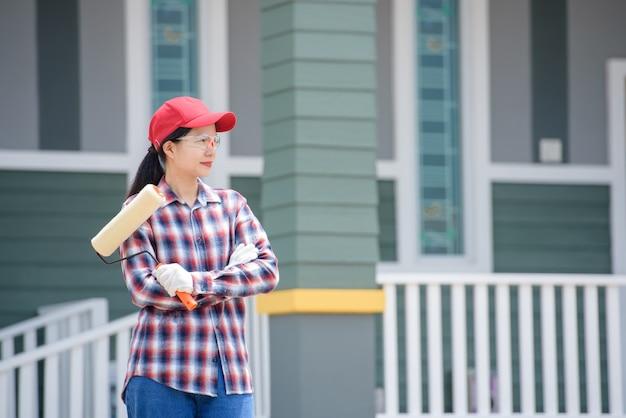 집 화가 인 아시아 여성 노동자 자신있게 페인트 롤러 붓을 들고 서십시오.