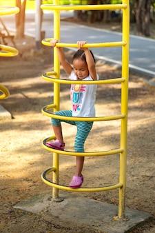 アジアの女の子が学校の遊具に登っています。