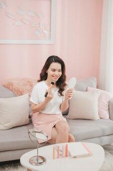 아시아 소녀가 화장품 메이크업을 사용하고 있습니다. 이것은 삶의 스타일입니다. 방에서의 메이크업은 좋은 것입니다.