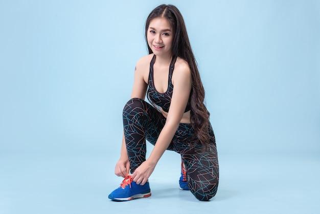 パステルブルーのスタジオシーンで運動するためにレギンスを履き、靴を履いているアジアの女の子。