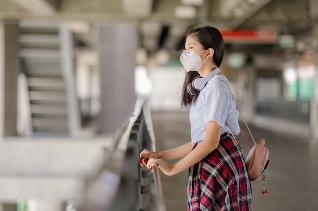 마스크를 쓴 아시아 소녀가 인도교에서 낙담한 채로 걷고 있습니다.