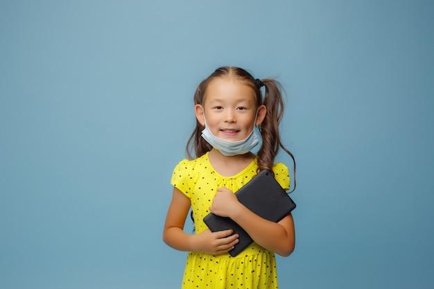 彼女の顔にマスクを持つアジアの女の子は、スタジオで青い手にタブレットを持っています
