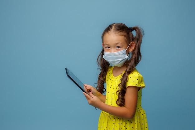 그녀의 얼굴에 마스크가있는 아시아 소녀는 파란색 스튜디오에서 그녀의 손에 태블릿을 보유하고 있습니다.