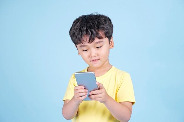 彼のモバイルスマートフォンにはまっているアジアのハンサムな小さな子供