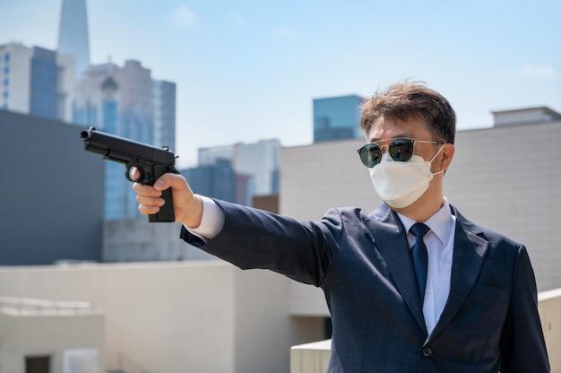 市内でサングラスとマスクを着用したピストルを持っているアジア人男性。