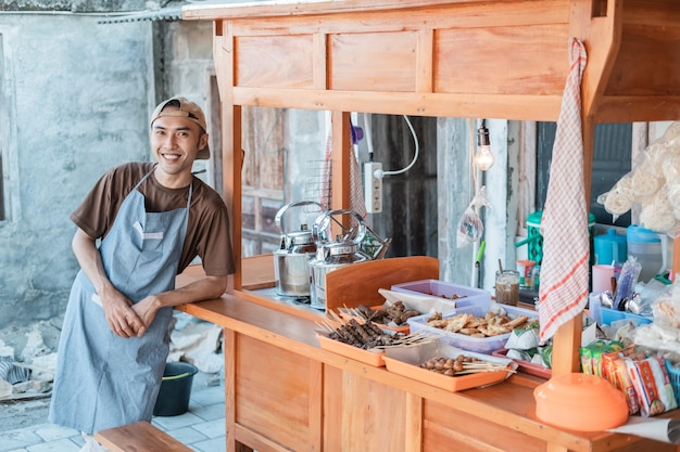 Официантка азиатского происхождения в фартуке стоит, опираясь о бок тележки