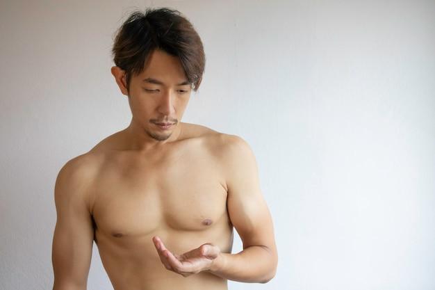 アジア人男性はシャツを着ず、手を胸に当てています。