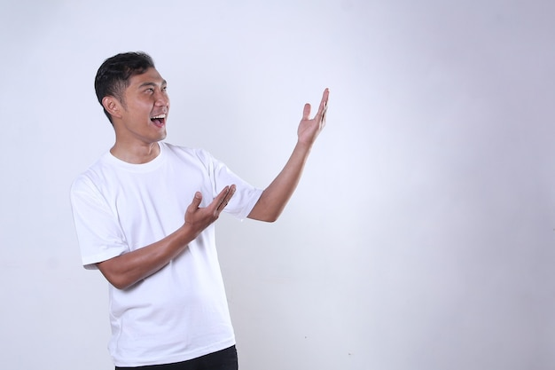 陽気な表情と何かを提示する白いシャツを着たアジア人男性