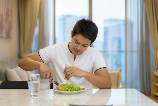 アジア人の男性が自宅の居間でアメリカンブレックファーストを食べています。