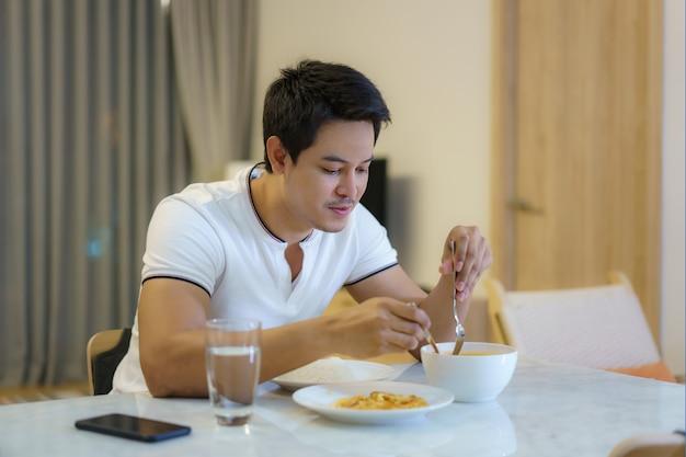 アジア人男性が自宅の夜の食卓で一人で夕食を食べています。