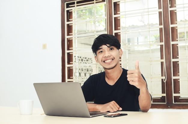アジア人男性が笑顔でノートパソコンの前に座っています