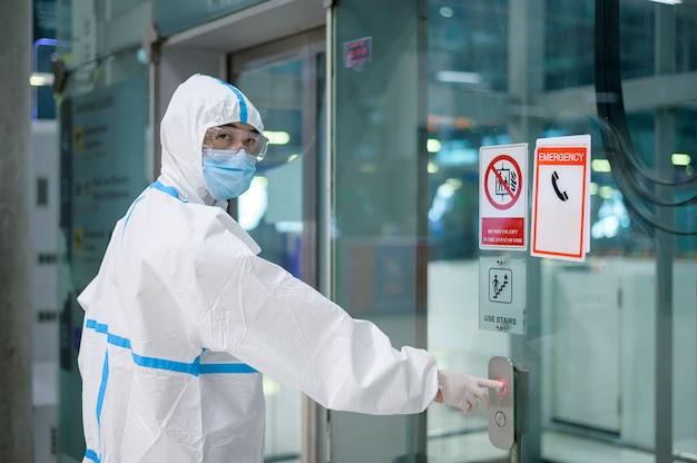 アジア人男性が空港のエレベーター、安全旅行、covid-19保護、社会的距離概念でppeスーツを着ています。