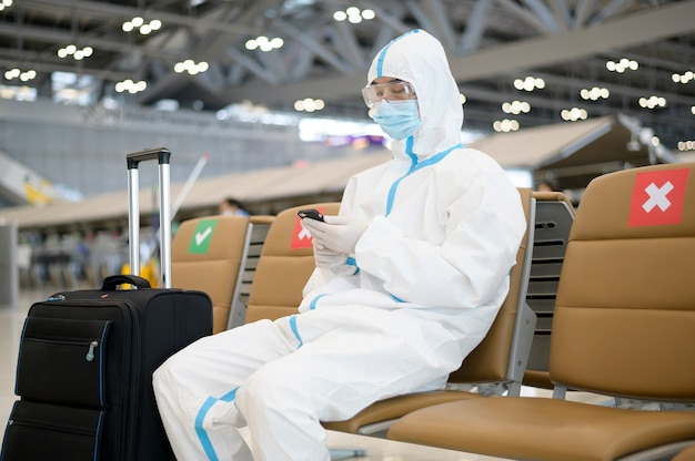 アジア人男性が国際空港、安全旅行、covid-19保護、社会的距離概念でppeスーツを着ています。