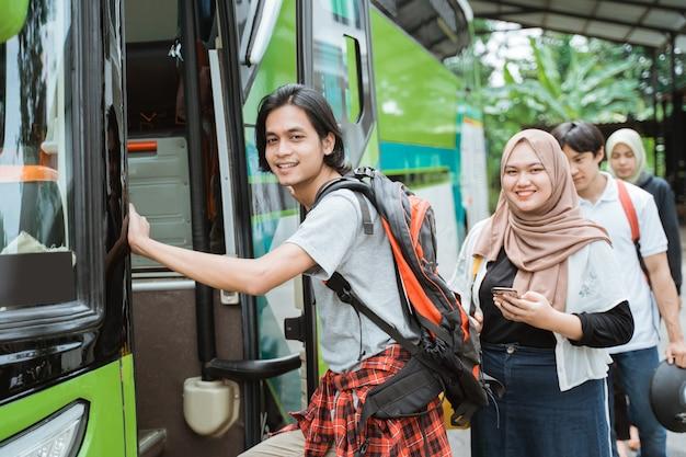문 손잡이를 잡고 배낭을 착용 한 아시아 남자가 버스에 타기 위해 줄을 서있는 승객의 배경으로 버스에 올라갑니다.