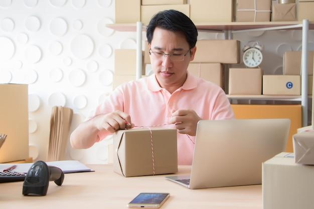 ピンクのシャツを着たアジア人男性がロープを結んで、自宅で注文した箱を詰めました