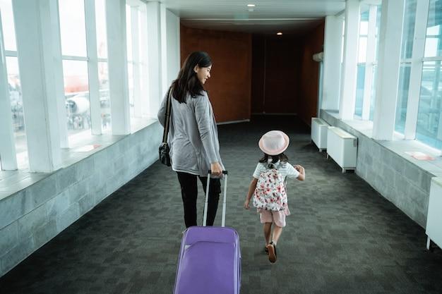 한 아시아 인 어머니와 딸이 걸어 와서 가방을 꺼내다