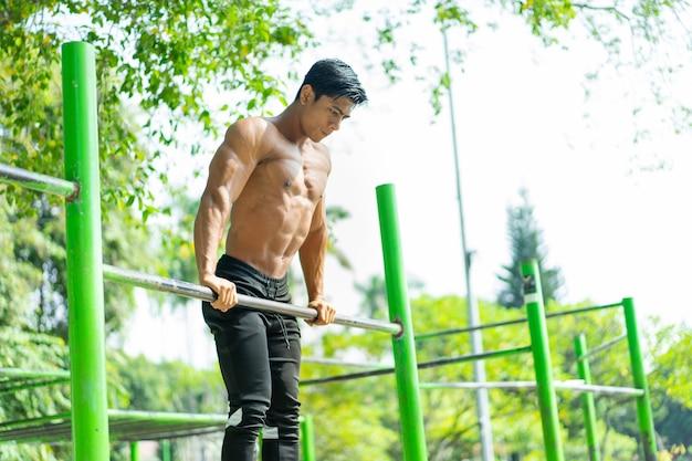 手で服を着ていないアジアの筋肉質の男性は、公園での登山力のための完璧な懸垂を行使します