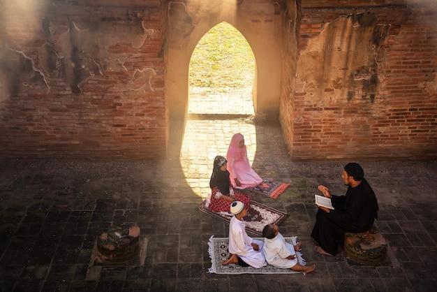 한 아시아계 이슬람 남성이 창문과 문을 통해 비치는 햇빛이 비치는 모스크에서 아들과 어린 딸에게 하느님께 드리는 기도문을 읽는 법을 가르쳤습니다.