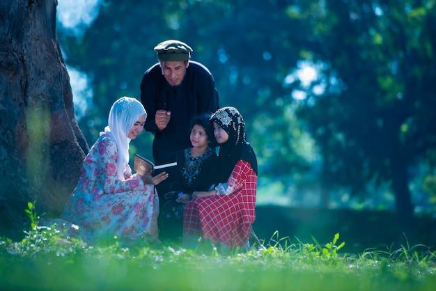 어린 딸을 가르치는 아시아계 이슬람 남성은 아침 햇살이 아름답게 비치는 집 잔디밭의 나무 아래에서 기도문을 읽습니다.