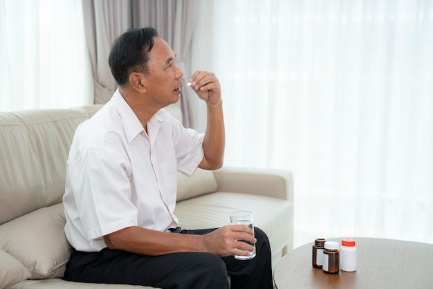 Азиатский старик собирается принять таблетки
