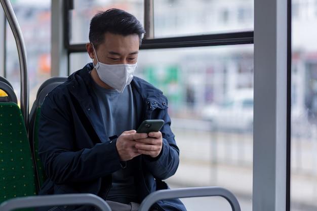 얼굴에 의료용 마스크를 쓴 아시아인 승객이 휴대전화로 걱정스럽게 글을 쓰고 뉴스를 읽고, 한 남자가 대중 교통 버스로 도시를 여행합니다.